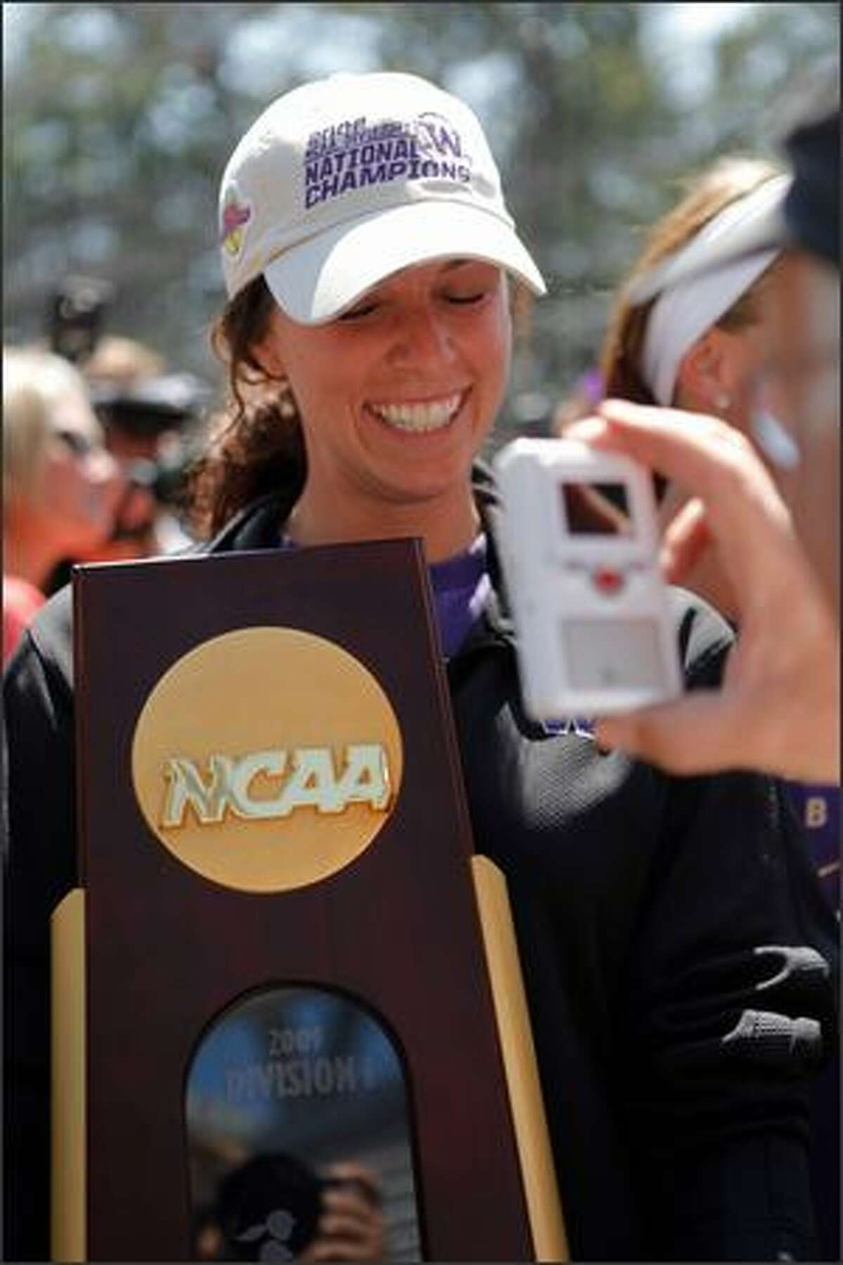 Lauren Greer smiles with the trophy after the Huskies returned home Wednesday.