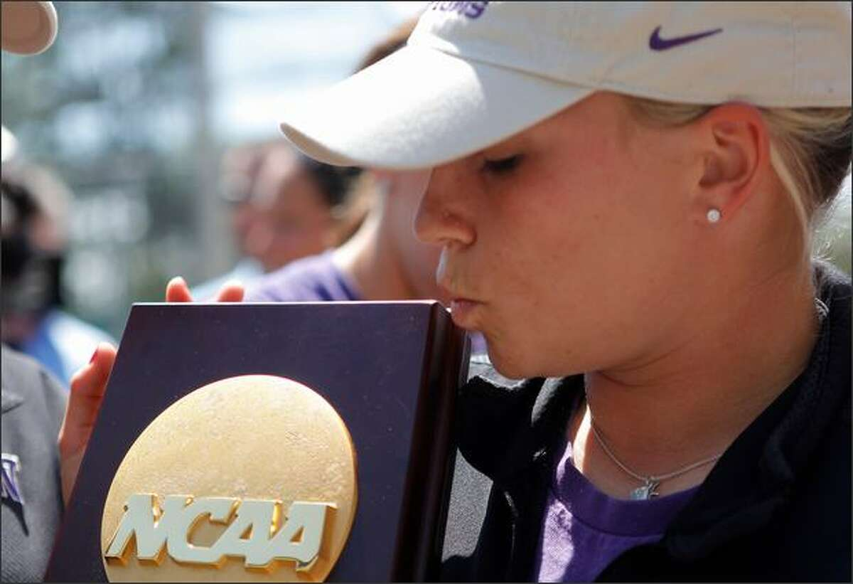 Ashlyn Watson kisses the trophy after the Huskies returned home Wednesday.