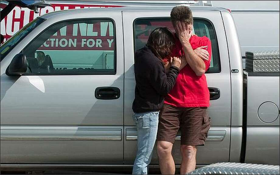 Stuart and Jackie Schuyler, the father and stepmother of Nick Schuyler, are seen at the Seminole Boat launch in Clearwater, Fla., on Sunday. The Coast Guard was searching off Florida's Gulf Coast on Sunday for a fishing boat carrying NFL players Corey Smith and Marquis Cooper and two other men, Will Bleakley and Nick Schuyler, missing nearly a day in choppy seas. Photo: / Associated Press