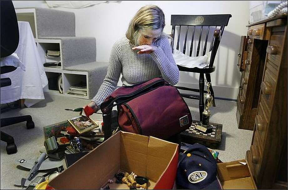 "Delaney Ruston is overcome with emotion while opening a box of items belonging to her late father, Richard Ruston, in her University District home. Ruston recently completed the film ""Unlisted"", a documentary about her father, who suffered from paranoid schizophrenia. Photo: Dan DeLong/Seattle Post-Intelligencer"