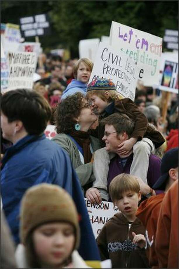 Connie Burk nuzzles her son, Henson Burk-Fawcett, on the shoulders of Burk's partner, Jake Fawcett. The Seattle couple journeyed to California to be married in 2004. Photo: Paul Joseph Brown, Seattle Post-Intelligencer