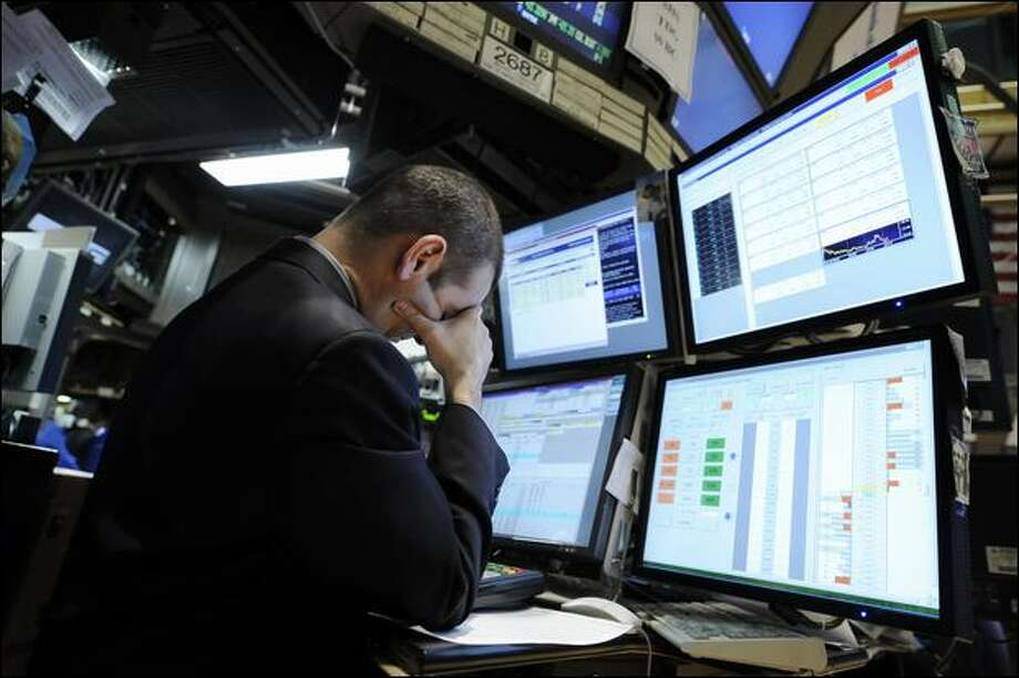 Michael Sollitto works at the New York Stock Exchange on Monday as the Dow falls. Photo: Richard Drew/Associated Press