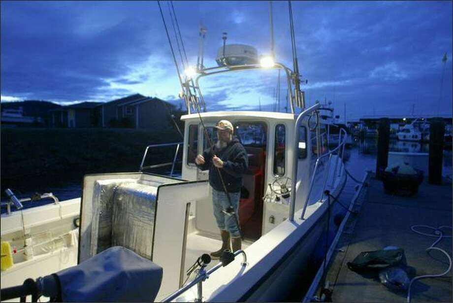 At daybreak, Jay Field readies his gear before heading out to fish. Photo: Gilbert W. Arias/Seattle Post-Intelligencer