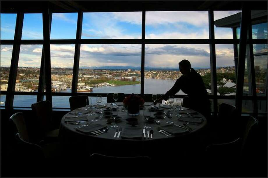With a beautiful view of Lake Union and Gas Works parks in the background, Wanda Mozzone sets the table for a private party. Photo: Scott Eklund/Seattle Post-Intelligencer