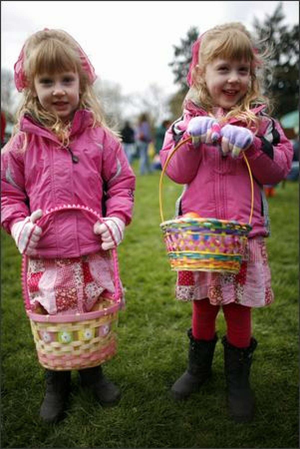 Miranda Marquardt, left, and her twin sister Marissa, both 4, show off their baskets.