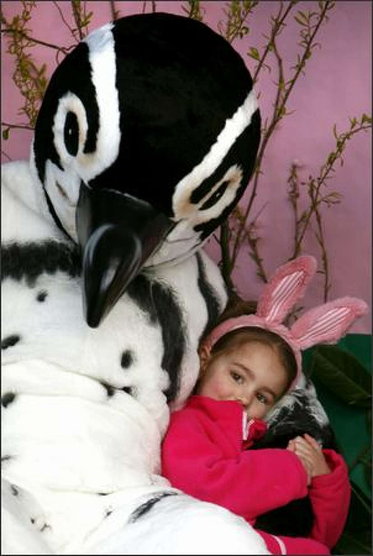 Mary Crowell, 4, sits with a penguin during the Woodland Park Zoo's Bunny Bounce.