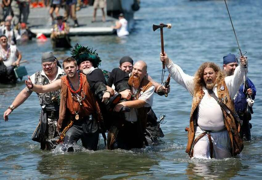A pirate is carried ashore as the Seafair Pirates land at Alki Beach in West Seattle in one of the traditional rituals kicking off Seafair.