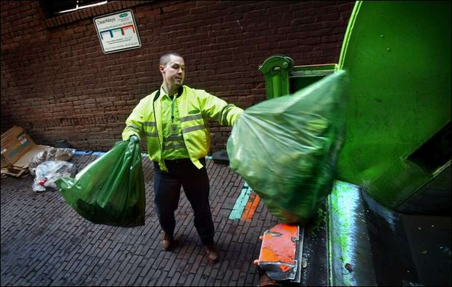 CleanScapes employee Jeremy Simatic tosses trash contained in prepaid bags Monday into his truck in the alley alongside Chuck's Hole in the Wall Barbeque in Pioneer Square. Seattle's new Clear Alleys program will ban the permanent storage of Dumpsters in alleys or sidewalks in downtown, Belltown and Pioneer Square. Instead, businesses will put refuse, recycling and compost in prepaid bags that are collected up to three times each day. Photo: Andy Rogers/Seattle Post-Intelligencer