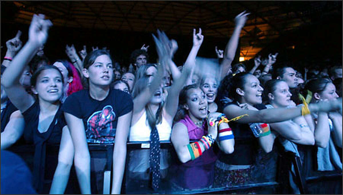 Fans of pop star Avril Lavingne watch and sing along as the blue lights spill on them during her show at the Tacoma Dome.
