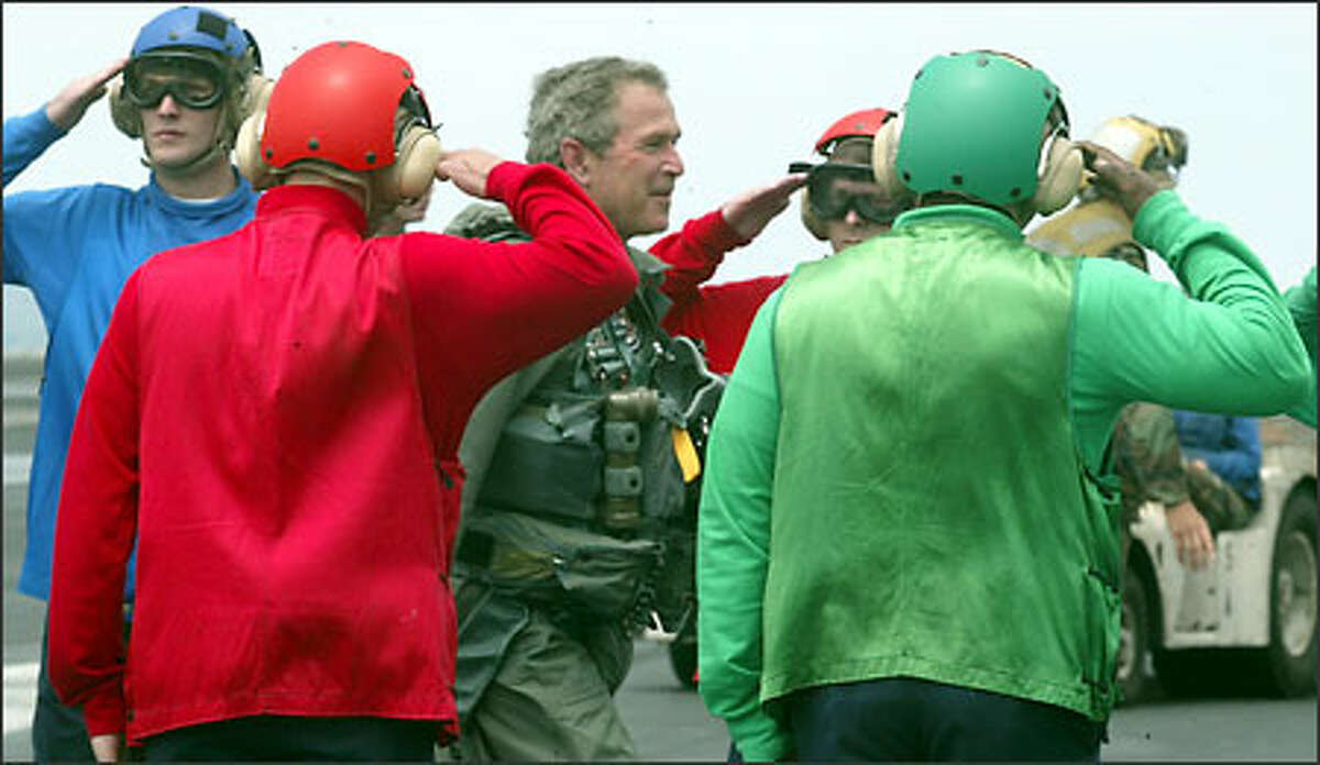 President George W. Bush is welcomed aboard by side boys dressed in the colors of the flight deck crew. President Bush visited the carrier as it headed towards San Diego after its tour of duty in the Persian Gulf.