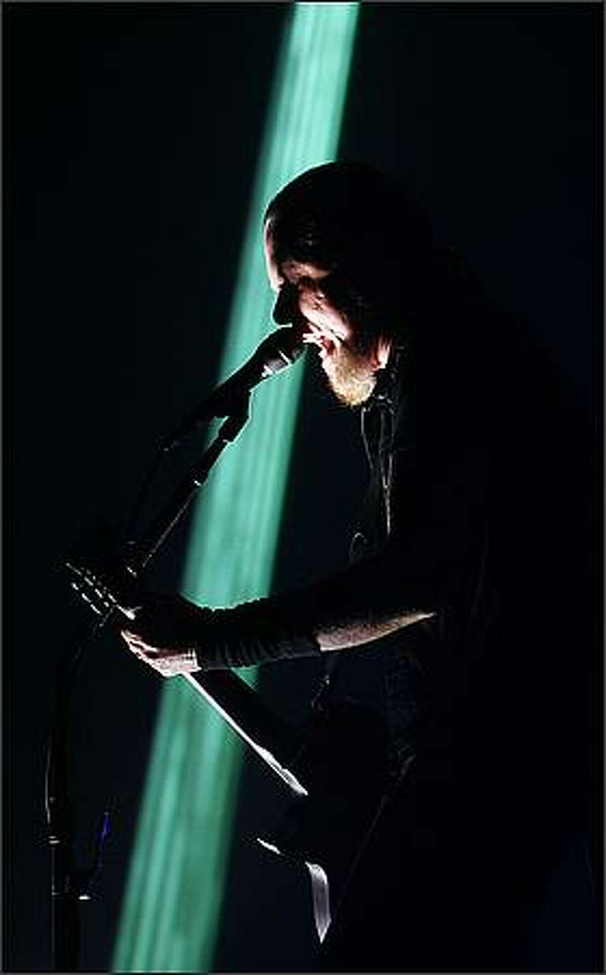 Metallica's lead vocalist James Hetfield sings silhouetted against a sliver of laser light at KeyArena in Seattle during Monday's concert.