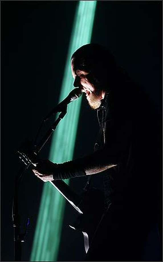 Metallica's lead vocalist James Hetfield sings silhouetted against a sliver of laser light at KeyArena in Seattle during Monday's concert. Photo: Mike Urban, Seattle Post-Intelligencer