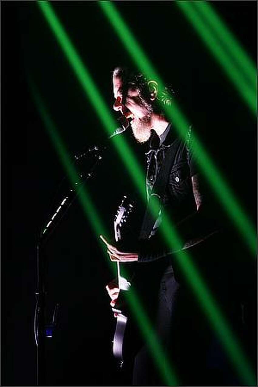 Metallica's lead vocalist James Hetfield sings within a cage of laser light at KeyArena in Seattle.
