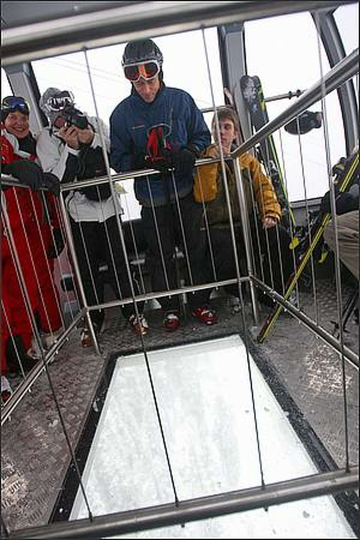 Gondola riders Bob Griffiths, center, and son Andrew, right, from Whistler, enjoy the view from one of two glass-bottomed cabins on the Peak2Peak Gondola in Whistler, British Columbia.