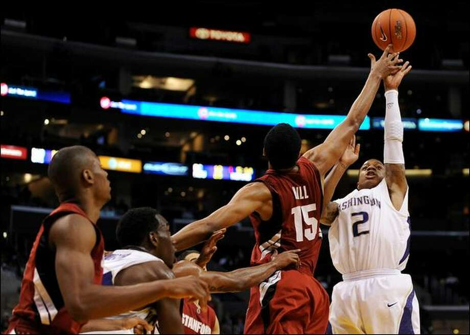 Huskies guard Isaiah Thomas puts up a shot over the outstretched hand of Stanford forward Lawrence Hill. Thomas finished with 14 points. Photo: Harry How/Getty Images