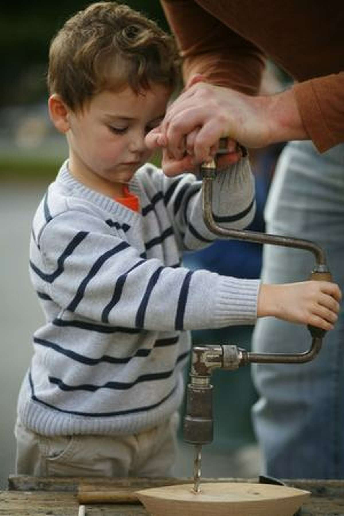 Reason Israel, 4, works on a wooden toy boat on Friday August 7, 2009 at the South Lake Union Block Party in Seattle.