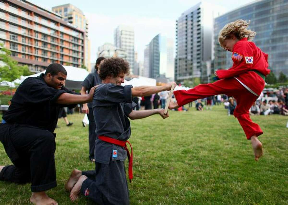 Jim O'Donnell holds a board as his son Wynn, 10, attempts a kick during a presentation by Quantum Martial Arts on Friday August 7, 2009 at the South Lake Union Block Party in Seattle.