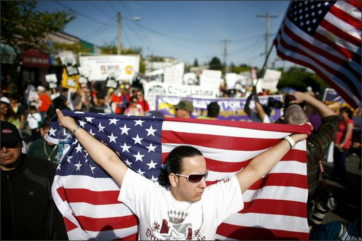 Hector Solano of El Salvador holds the U.S. flag as he marches in the annual May Day march and rally in downtown Seattle on Friday, May 1, 2009. Marchers called for immigration reform and worker rights.