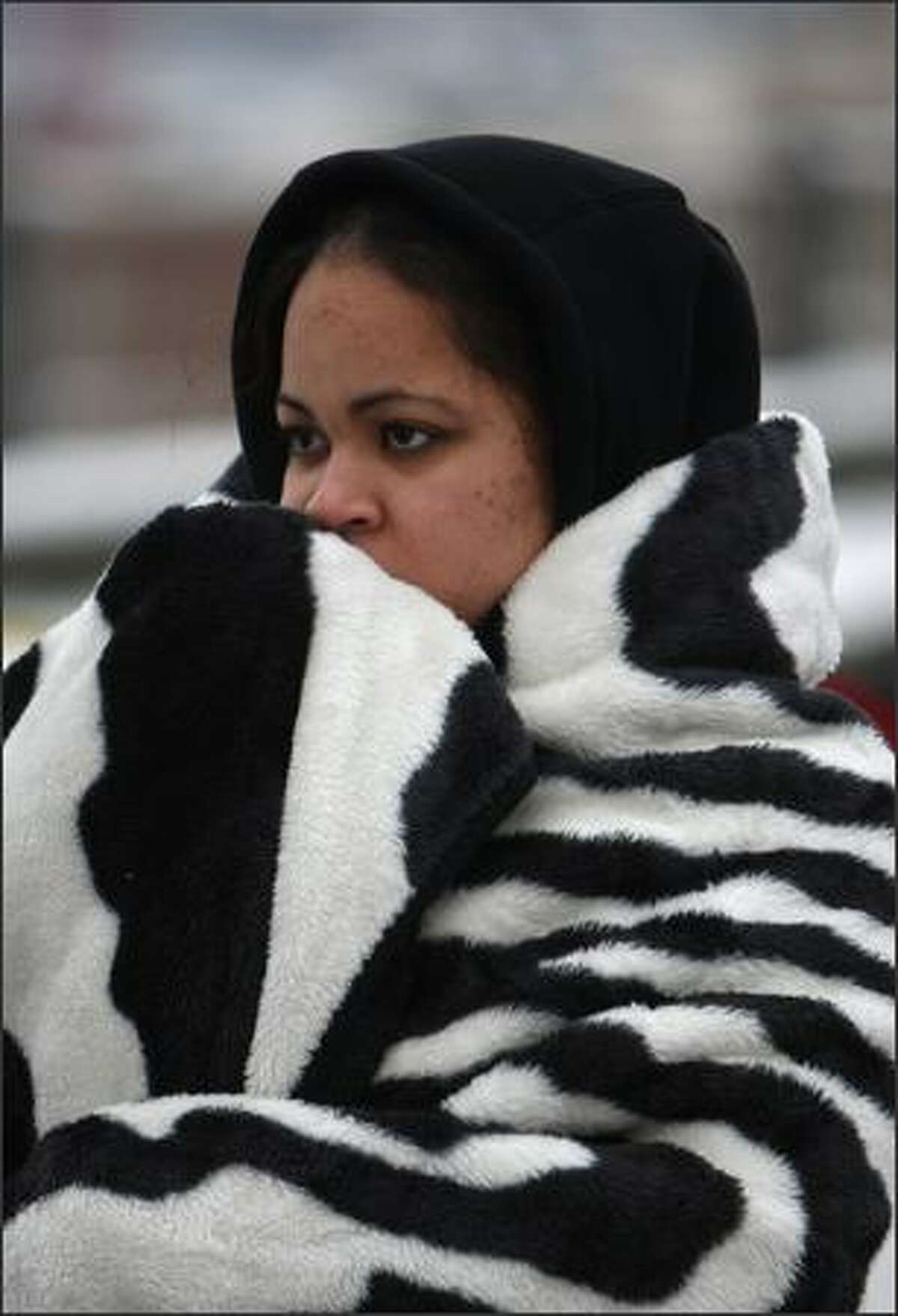 Passenger Stephanie McCullough waits to get her luggage at the scene of an accident where two charter buses with dozens of people aboard slid down the snow-covered cobblestones of East Thomas Street on Capitol Hill and crashed into each other.