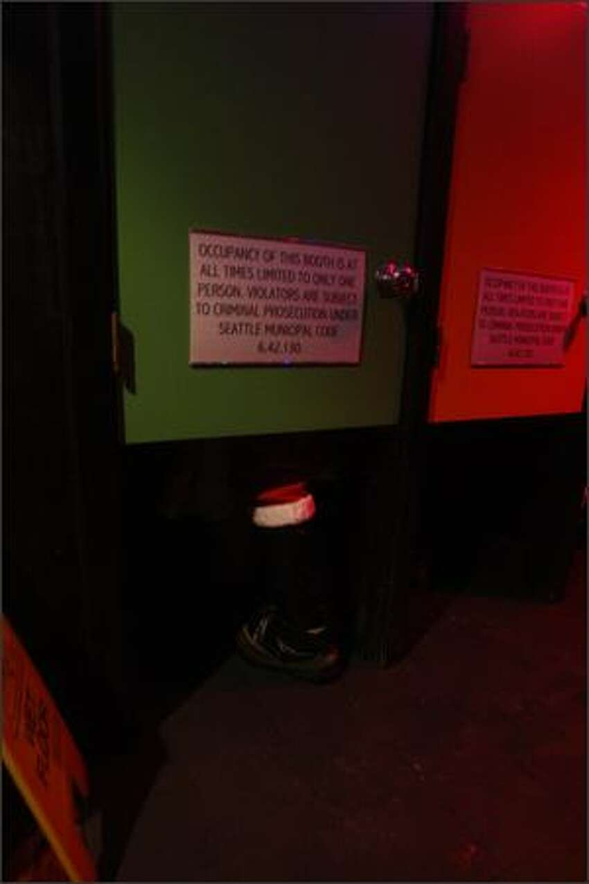 Santas take in a peep show at the Lusty Lady.