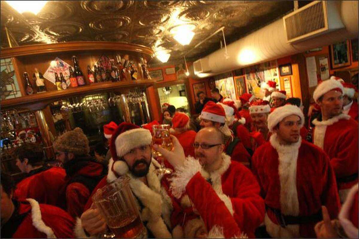 Santarchy revelers toast the season at Pike Pub and Brewery in Seattle on Saturday. Santarchy is an annual Seattle holiday pub crawl.