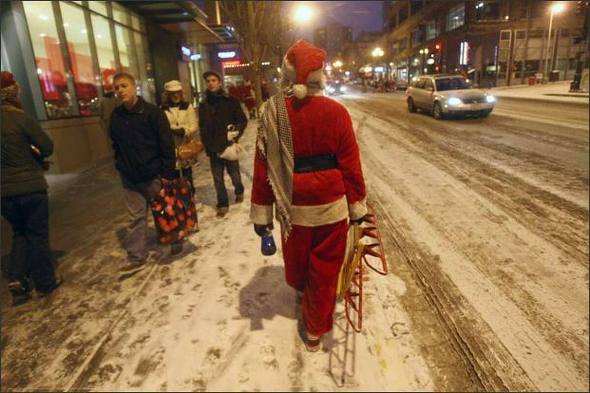 A lone Santa follows the pack of fellow Santarchy revelers on their way to Pike Pub and Brewery.