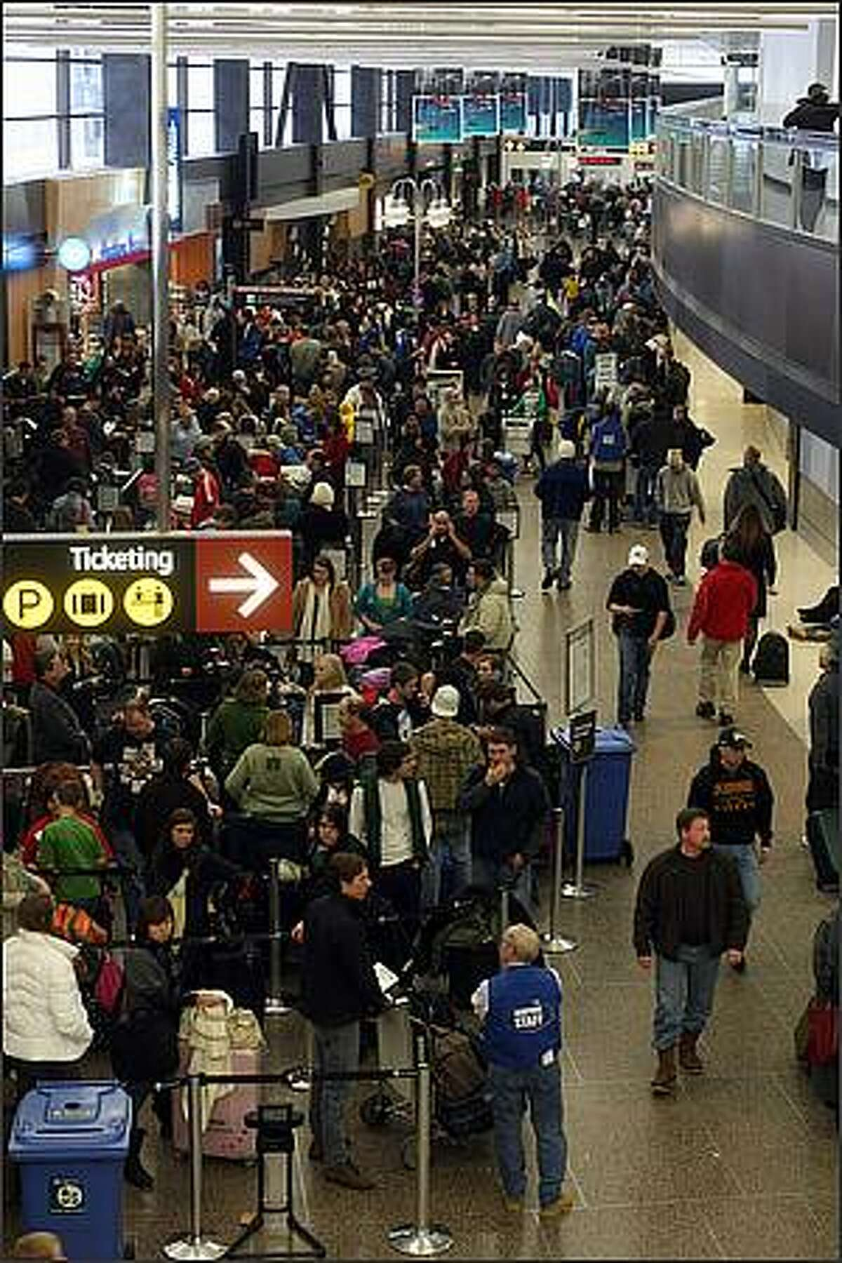 Passengers wait in long lines at a security checkpoint at Sea-Tac Airport.