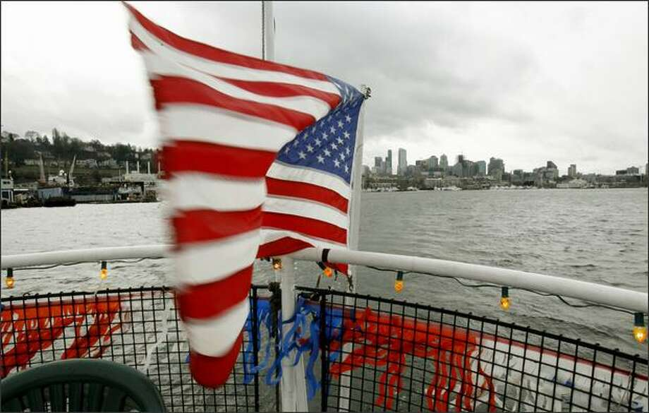 Aboard the Fremont Avenue, a U.S. flag waves in a brisk wind during a Sunday Ice Cream Cruise on Lake Union. Photo: Dan DeLong/Seattle Post-Intelligencer
