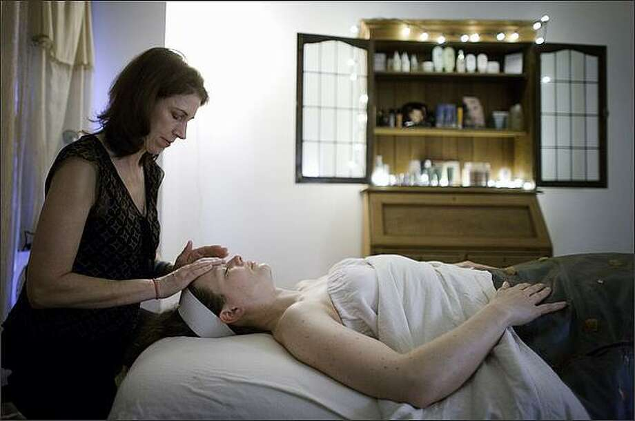 """Lisa Steele, owner of Cassie's Place Skin Care, gives a facial to Barbara Sweeney on Saturday March 14, 2009 in Ballard. Steele has two unique payment programs at her business. """"Let's make a deal,"""" which allows customers to name a price, and """"Pay it forward,"""" where her services are free as long as customers do something nice for someone else. Photo: Joshua Trujillo/Seattle Post-Intelligencer"""