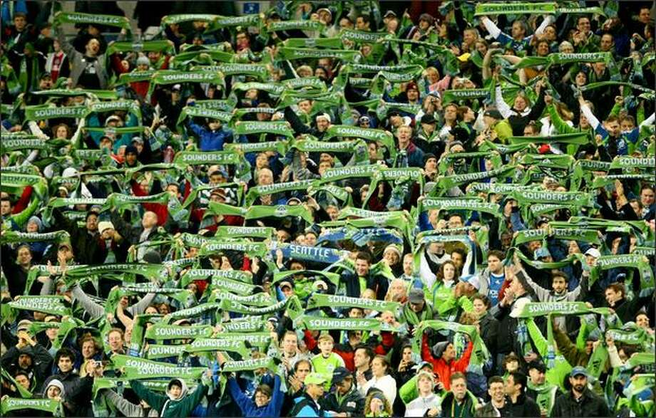 Just like other soccer fans throughout the world, Sounders FC fans raise their scarves in support of their side. Photo: Joshua Trujillo/Seattle Post-Intelligencer