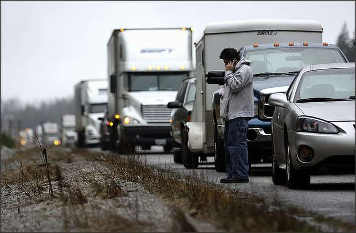 Jonathan Gutierrez of Renton talks on the phone while waiting on the shoulder of I-90 where it was closed at North Bend due to heavy snowfall on Snoqualmie Pass on New Year's Day. Gutierrez was trying to drive to Spokane for work. He was planning to wait on the shoulder for three hours before turning around in hopes that the pass would be reopened.