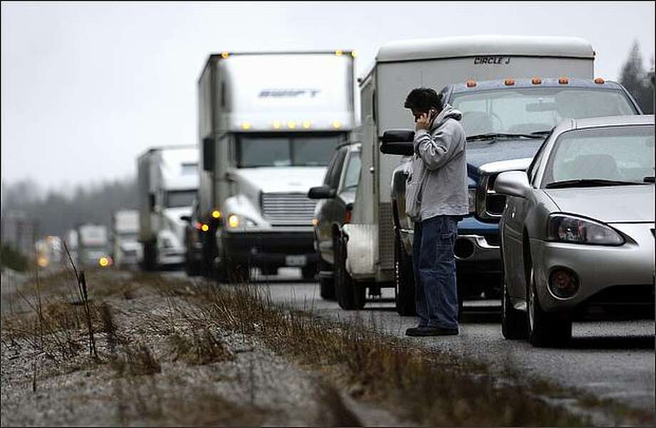 Jonathan Gutierrez of Renton talks on the phone while waiting on the shoulder of I-90 where it was closed at North Bend due to heavy snowfall on Snoqualmie Pass on New Year's Day. Gutierrez was trying to drive to Spokane for work. He was planning to wait on the shoulder for three hours before turning around in hopes that the pass would be reopened. Photo: Andy Rogers, Seattle Post-Intelligencer