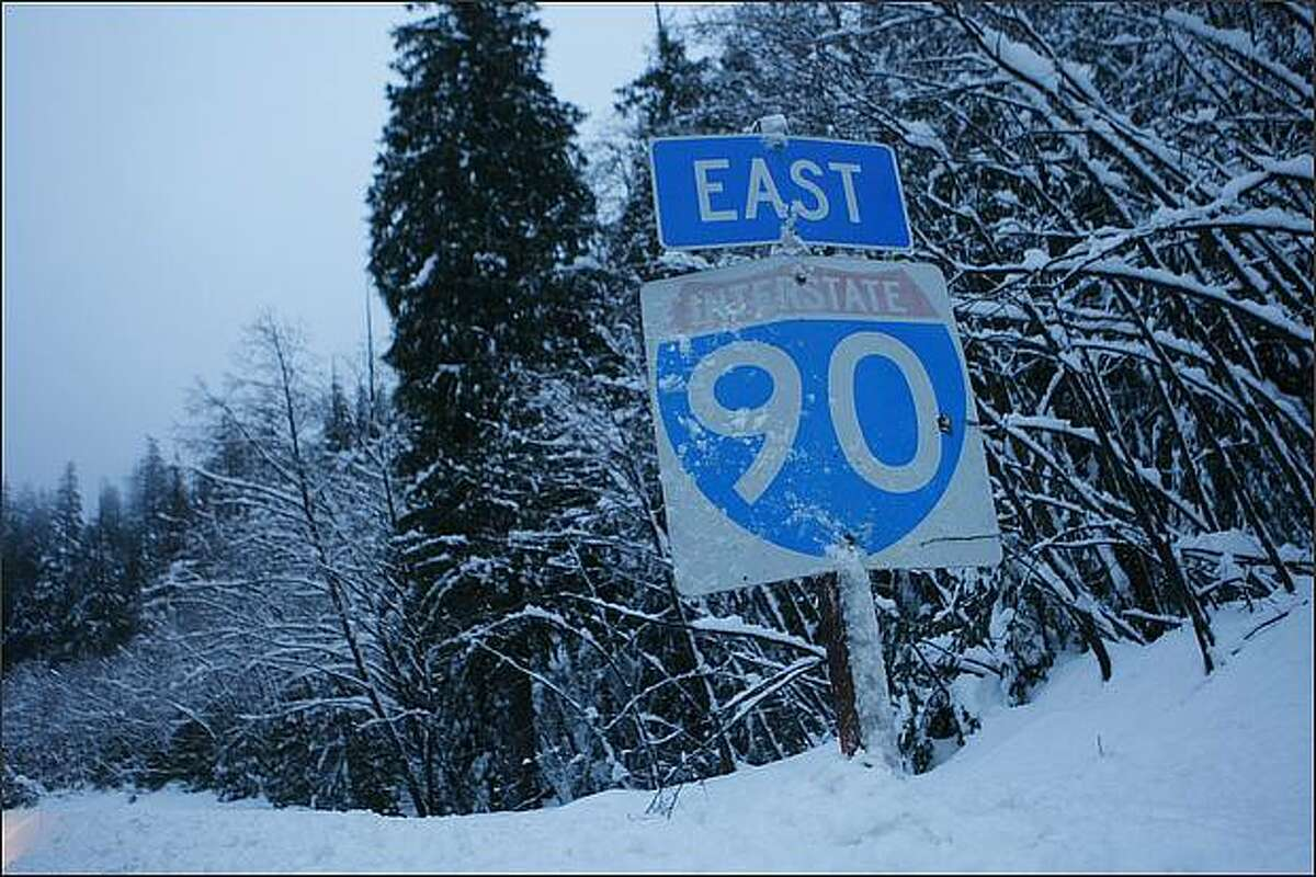 Snow nearly buries a sign alongside of the eastbound lanes of I-90 near exit 52 on Thursday.