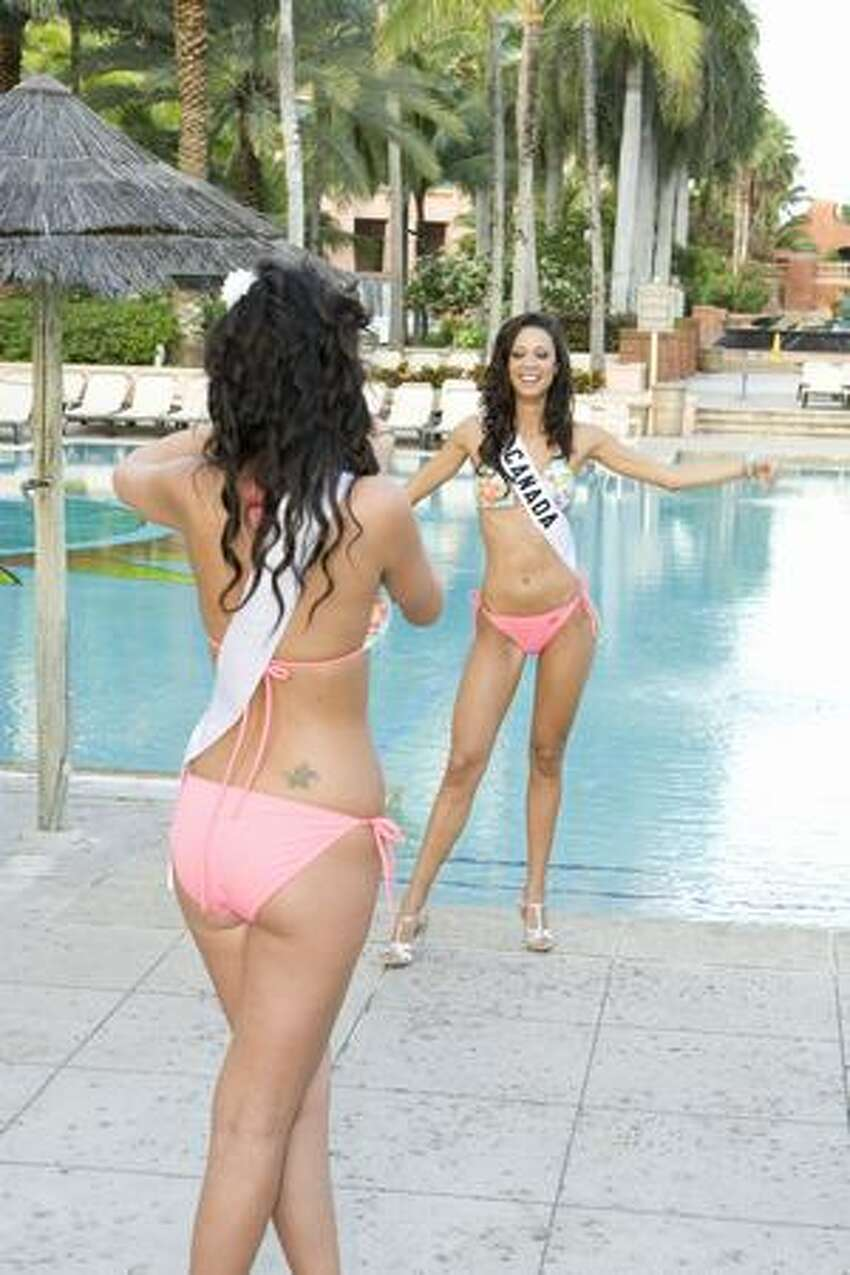 Dominique Peltier, Miss Bolivia, takes a photo of Mariana Valente, Miss Canada, at the Atlantis resort, headquarters for the pageant.