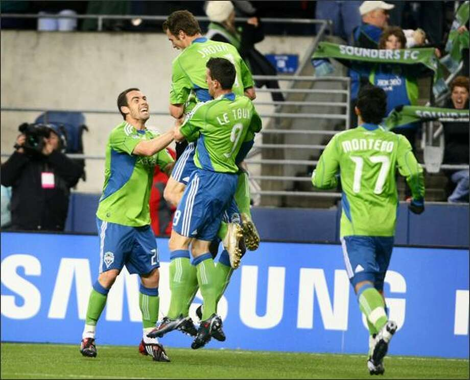 Sounders FC players, from left, Zach Scott (20) and Sebastien Le Toux (9) leap with Nate Jaqua (21), top, after Jaqua scored a goal in the first half against Real Salt Lake. Photo: Joshua Trujillo/seattlepi.com