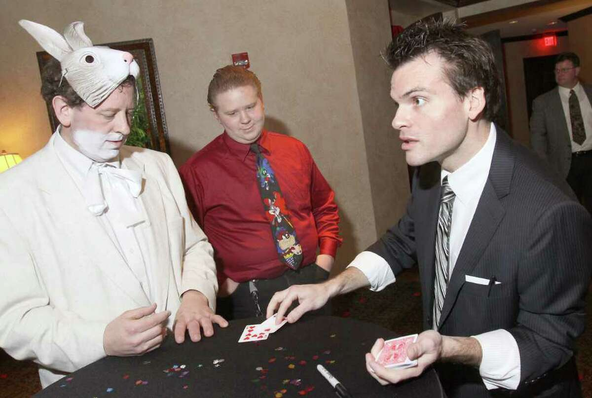 Card magician Jason Ladanye, right, does his best to impress Robert, left, dressed as the White Rabbit, and Nick Biales with a card trick. Saratoga Springs, NY - March 19, 2011 (Photo by Joe Putrock / Special to the Times Union)