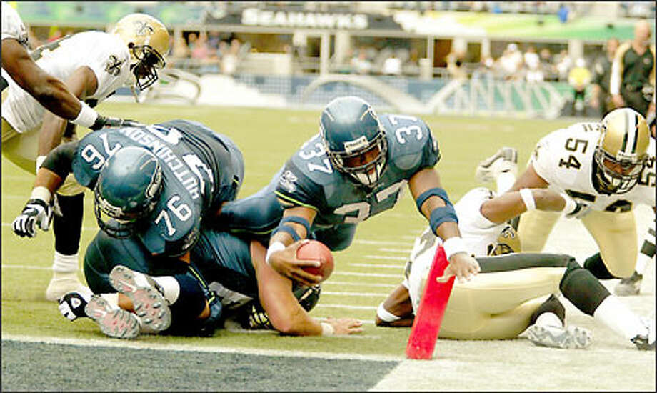 Shaun Alexander, center, dives into the end zone against the Saints after hauling in a 10-yard pass from Matt Hasselbeck with 24 seconds remaining in the second quarter of Seattle's 27-10 victory. Photo: Mike Urban, Seattle Post-Intelligencer