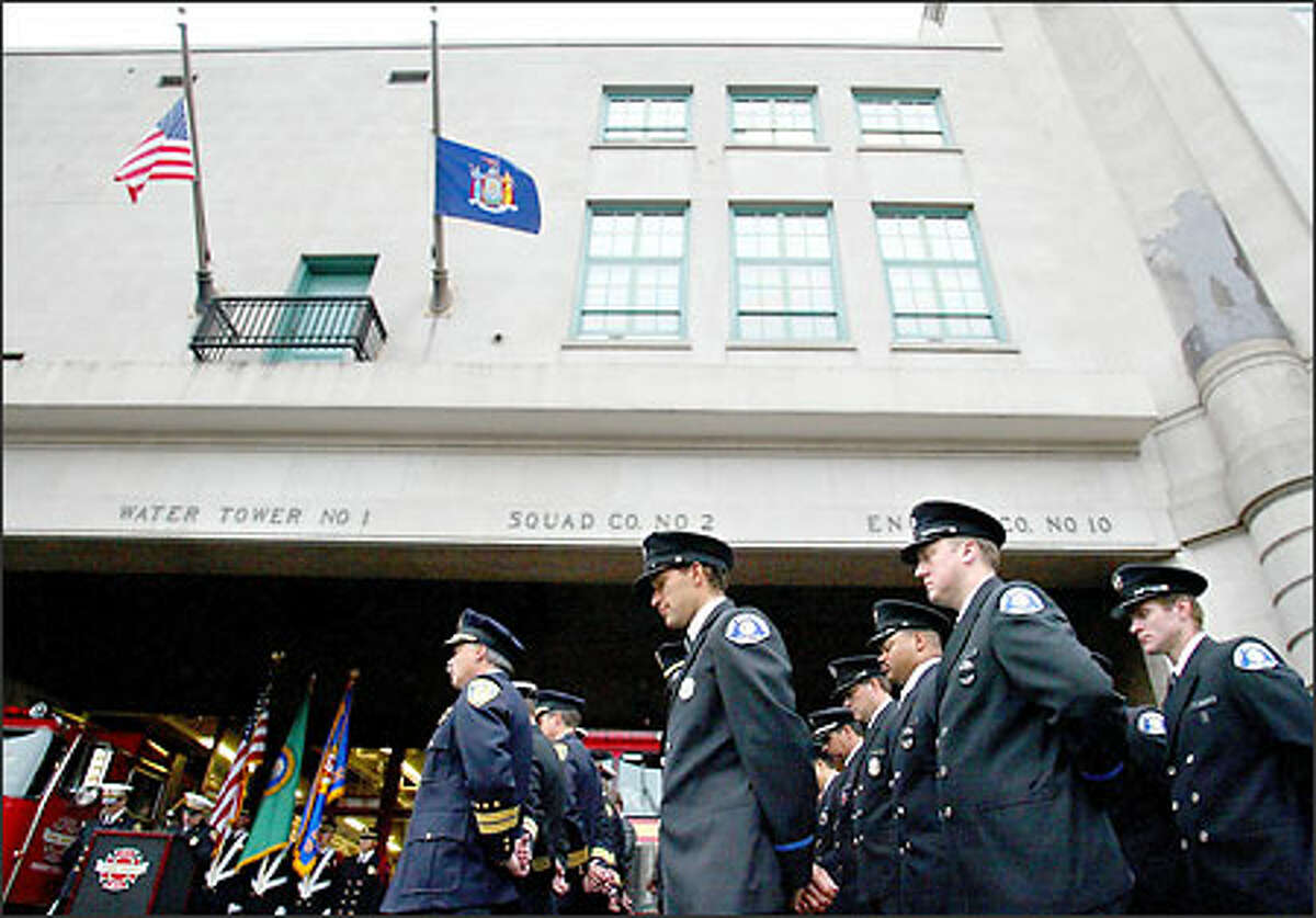 Seattle firefighters bow their heads during a moment of silence at Fire Station 10 in memory of those killed in the terrorist attacks on Sept. 11, 2001. The American and New York state flags are flying at half staff at the firehouse as part of the department's remembrance.