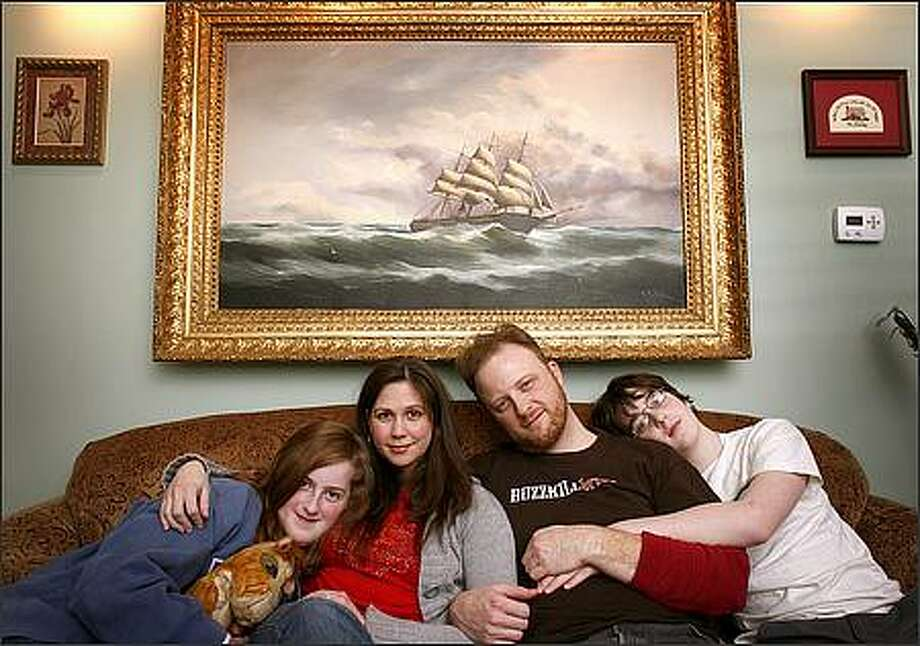 Kayleigh Downing, Raechelle Marsh, Todd Downing and Tyler Downing relax on the couch of their rebuilt home on April 2. Above them is an heirloom painting that survived the flood and then the fire that destroyed their house. Photo: Joshua Trujillo/Seattlepi.com