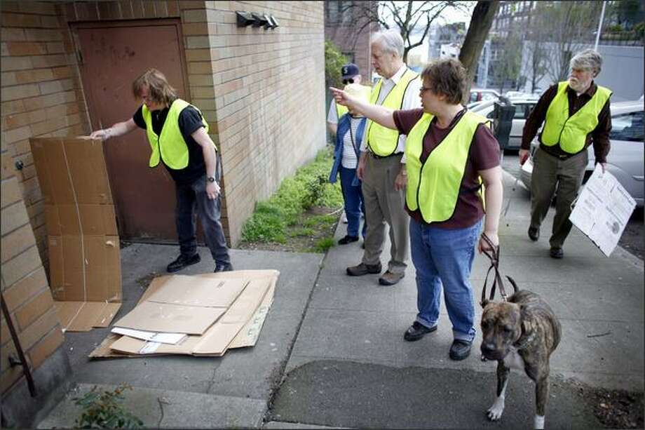 Members of Belltown COP, including Brett Paulson, left, and Janet Welt, with her dog Dolly, clean up cardboard left in a doorway during a community patrol on Second Avenue. Photo: Joshua Trujillo/seattlepi.com