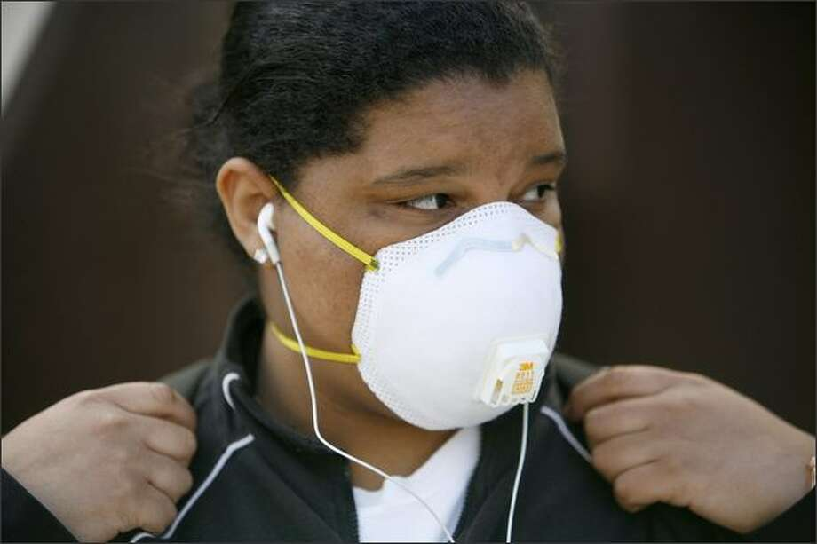 Kendra Davis, 18, wears a medical mask as she waits for a King County Metro bus at 23rd Avenue East and East Madison Street on Thursday. Davis said her morning bus ride scared her when a passenger on the bus had a coughing fit and did not cover his mouth. Photo: Joshua Trujillo/seattlepi.com