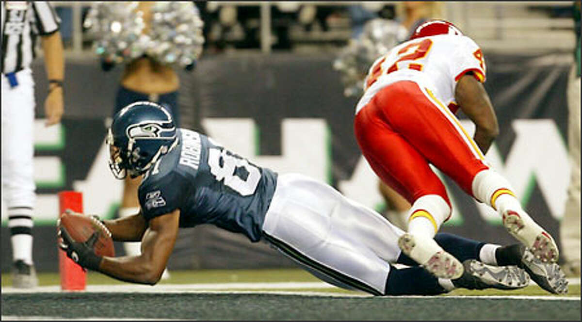 Seahawks Koren Robinson hauls in a 19 yard touchdown from Trent Dilfer in front of Chiefs Shaunard Harts during third quarter.
