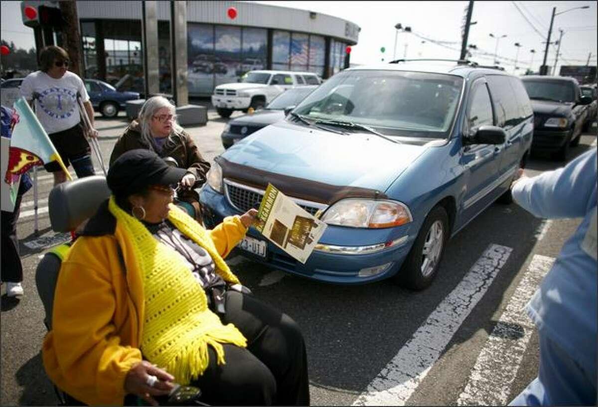 A car continues to roll into the crosswalk, bumping a marcher as Brandy Sebron-Kelley, in yellow, and other members of nearby senior citizens' residential buildings protest in the crosswalks at the intersection of Aurora Avenue North and North 130th Street. Sebron-Kelley was previously hit by a car at North 130th Street and Linden Avenue North.