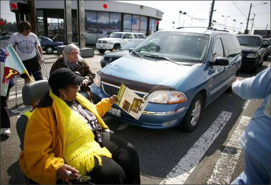 A car continues to roll into the crosswalk, bumping a marcher as Brandy  Sebron-Kelley, in yellow, and other members of nearby senior citizens'  residential buildings protest in the crosswalks at the intersection of  Aurora Avenue North and North 130th Street in 2009. Sebron-Kelley was previously  hit by a car at North 130th Street and Linden Avenue North. Photo by Joshua Trujillo/seattlepi.com. Photo: Joshua Trujillo/seattlepi.com