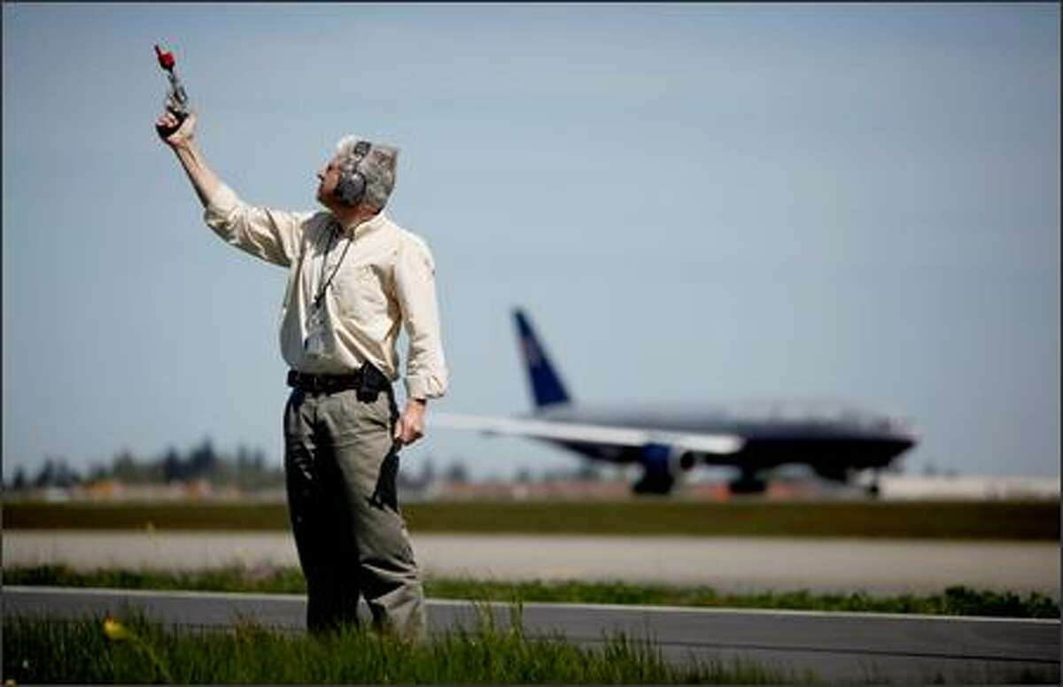 Steve Osmek, biologist and wildlife program manager at Sea-Tac Airport, prepares to launch pyrotechnics designed to scare off birds that fly too close to planes. · Photo gallery