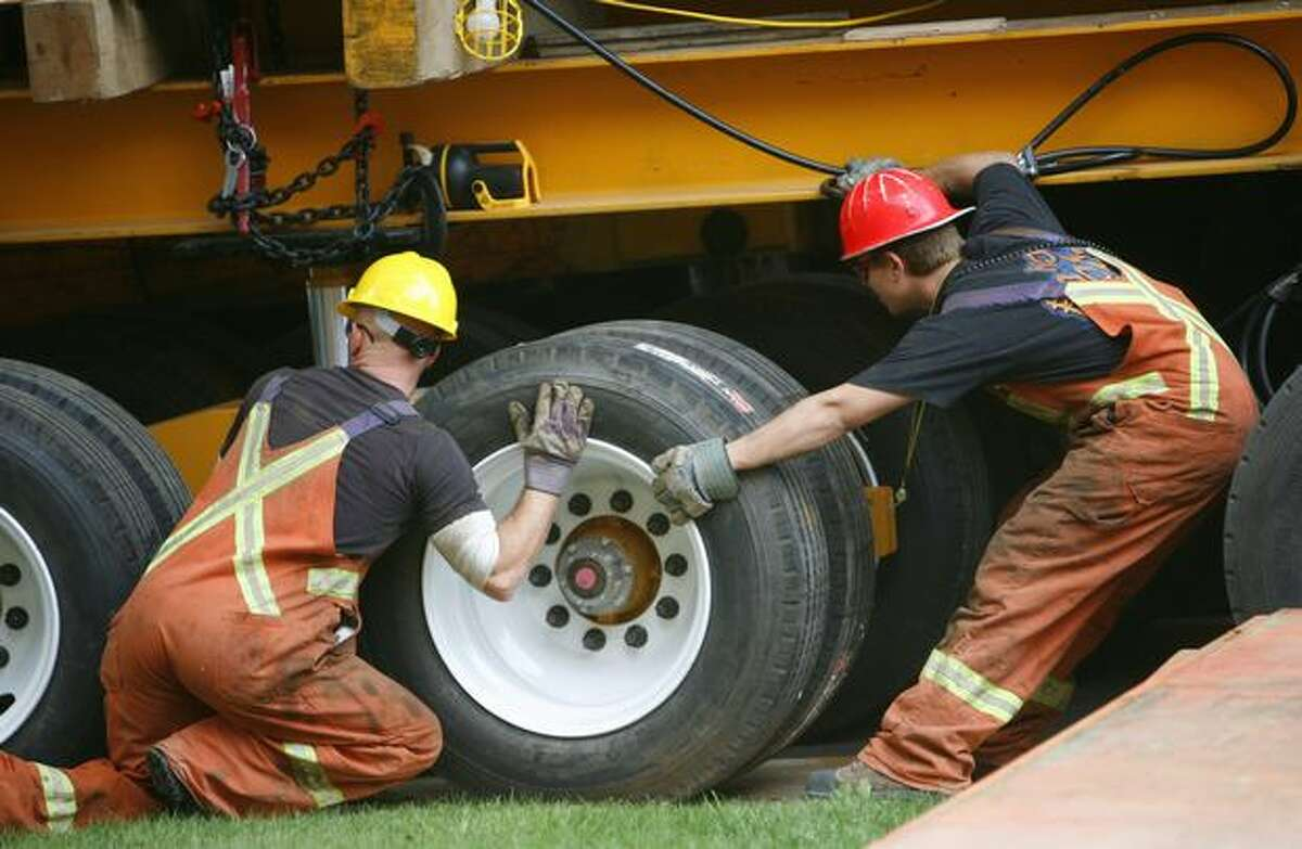 Workers from Nickel Bros. align wheels under the University of Washington's Cunningham Hall during a relocation of the 250 ton building on Wednesday September 16, 2009.