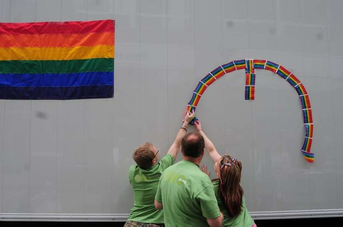 From left, Rob Reid, Dennis Prescott and India May work to tape flags to the Group Health truck before the start of the Seattle Pride Parade through downtown Seattle on Sunday.