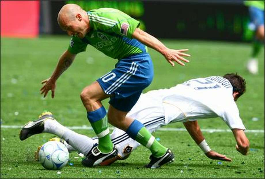 Seattle Sounders player Freddie Ljungberg tangles with Los Angeles Galaxy player Alan Gordon (21) on Sunday during the first half at Qwest Field in Seattle. Photo:  Joshua Trujillo/Seattlepi.com