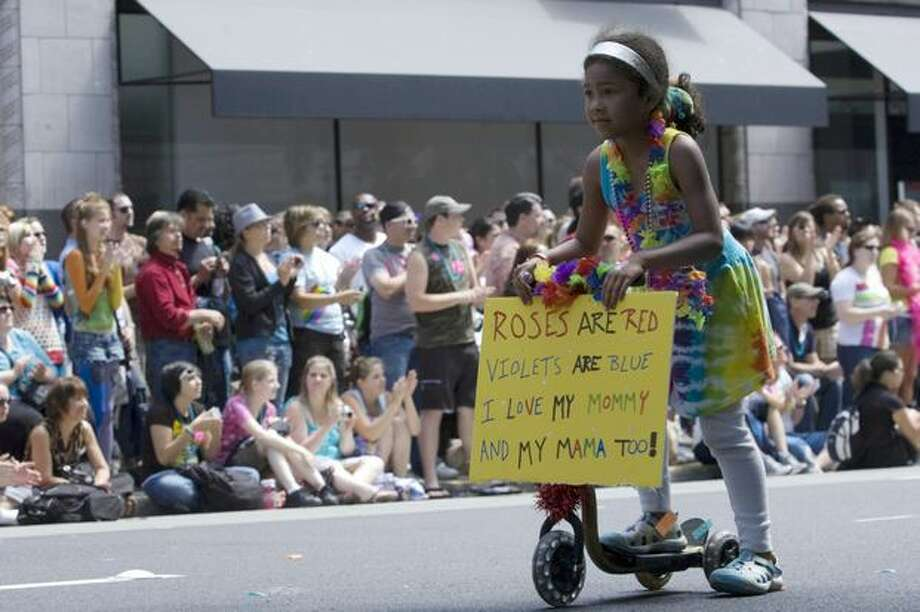A young girl rides in the parade bearing a sign during the Seattle Pride Parade. Photo: Daniel Berman, Seattlepi.com