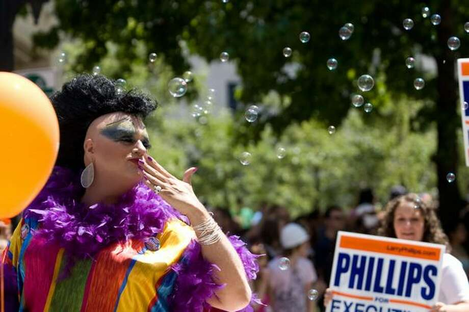 A participant with the Larry Phillips float waves to the crowd during the Seattle Pride Parade. Photo: Daniel Berman, Seattlepi.com
